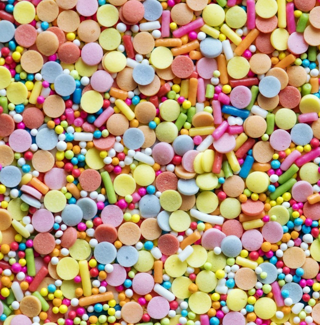 Flat lay of colorful rainbow sparkle candies of different shapes and sizes